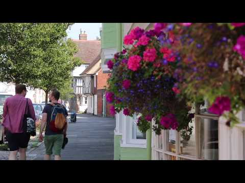 Tourists walking in Faversham, next to flowers on a shop.