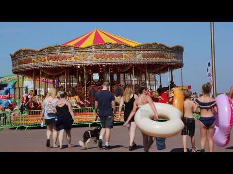 People walking towards a carousel.