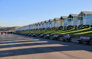 People walking at Minster Leas in front of beach huts.